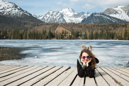 Young girl is lying on wooden terrace by frozen mountains lake Strbske pleso - spring time coming into High Tatras in Slovakia. Stock Photo