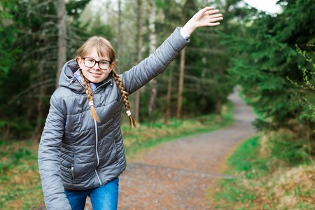 Young girl tourist in gray jacket on walking trail in th forrest - saluting with hand