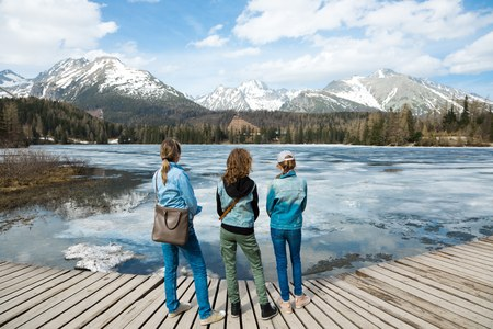Back view on three female tourists staying by frozen mountains lake - spring time coming into High Tatras in Slovakia.