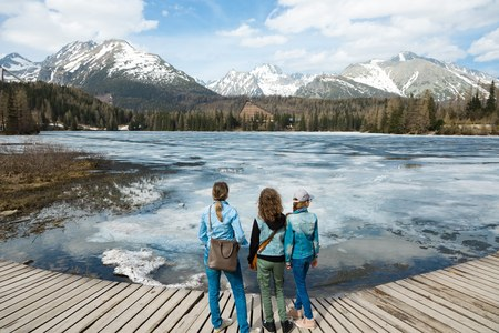Back wide view on three female tourists staying by frozen mountains lake Strbske pleso - spring time coming into High Tatras in Slovakia.