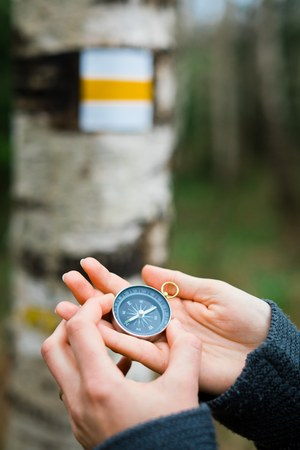 Womans hands using compass by tourist sign - looking for the right direction