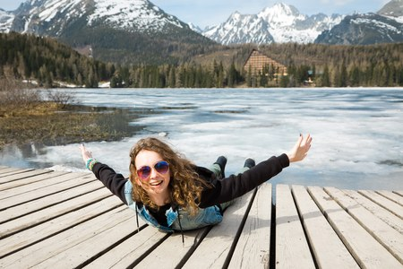 Young girl is lying by frozen mountains lake Strbske pleso and having fun - pretend flying like a bird - spring time coming into High Tatras in Slovakia. Stock Photo