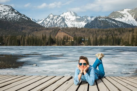 A woman in jeans lying by frozen mountains lake Strbske pleso - spring time coming into High Tatras in Slovakia.