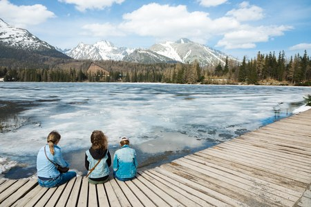 Back view on three female tourists sitting by frozen mountains lake Strbske pleso - spring time coming into High Tatras in Slovakia.