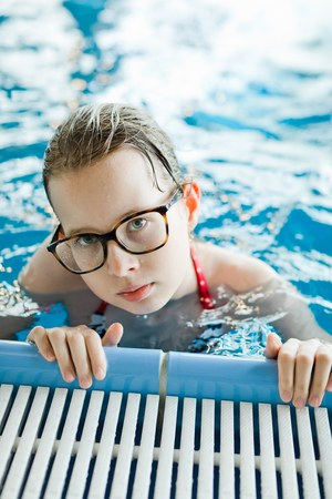 Young girl with glasses posing in pool holding the edge - healthy lifestyle activity during holiday Stock Photo