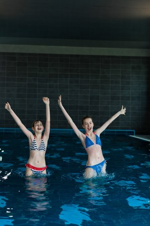 Teenaged girls jumping in indoor poll - hands up