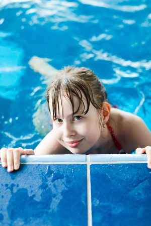 Young girl posing in pool holding on the edge - healthy lifestyle activity during holiday