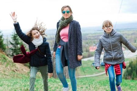 Female tourists reaching top - finishing long uphill trip.