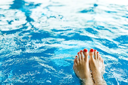 Womans feet with red pedicure in pool - attractive view on toes