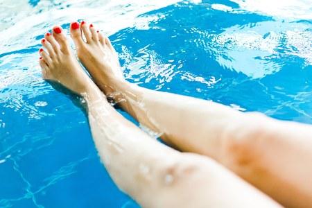 Jambe de femme avec pédicure rouge dans la piscine - jolie vue