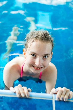 Young blond girl posing in pool holding the edge - healthy lifestyle