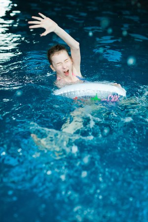 Helpless child drawing in indoor pool - danger during holiday