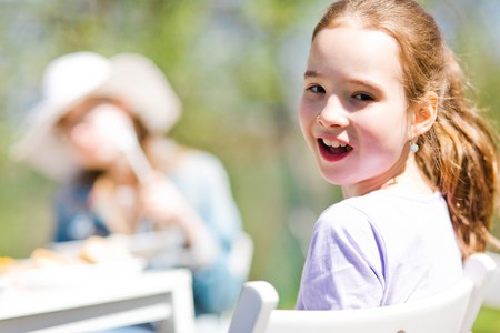 Teen aged girl sitting by table and looking back on birthday garden party - sunny day