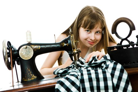 Teenaged girl tailoress use manual sawing machine to sew her dress - vintage tailor's tools used by young - concept on white background