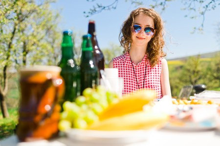 Teen aged girl in red checkered shirt sitting by table on birthday garden party - food and bottles on table - sunny day