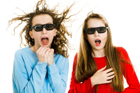 Two amazed teen girls in cinema wearing 3D glasses experiencing 5D cinema effect - wind blowing into faces - gestures of astonishment - concept on white background
