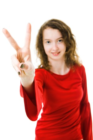 Slim girl in red dress showing victory sign with two fingers - focus on fingers, blurry face in background