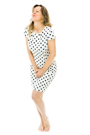 A woman in dot's dress urgently need toilet, necessity of peeing Stock Photo
