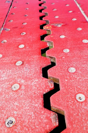 Close up view from above of an red iron dilatation joint placed on a opening bridge road - Zigzag line from steel
