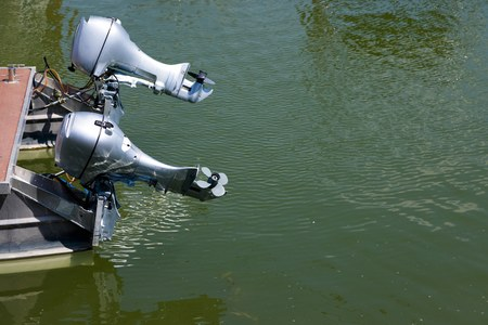 Pair of mid size boat engines out of water, silver bodies Stock Photo
