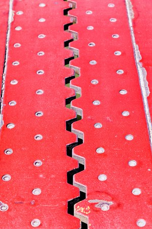 Top view from above of an red iron dilatation joint placed on a opening bridge road - Zigzag line from steel
