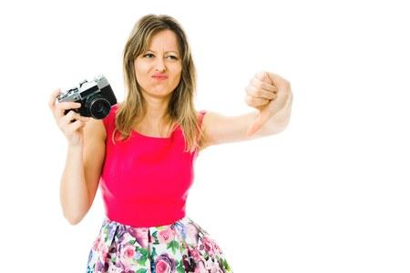 Kobieta w purpurowej sukience z zabytkową kamerą analogową pokazującą gest puchnięcia w dół