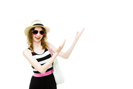 Young girl tourist in summer outfit pointing hands on white blanket space, area for traveling agency promotion