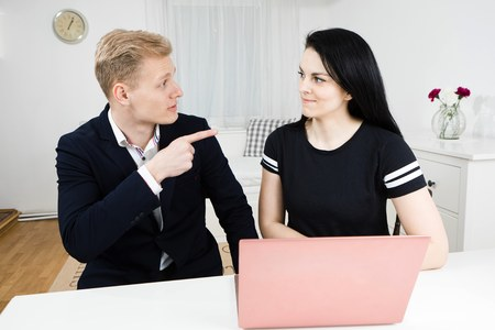 Superiors works with subordinate, blond man working with black haired woman, disputing emotionally