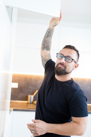A man with glasses and tattoo on his right hand in black T-shirt in modern white kitchen