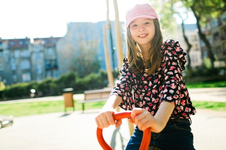 Child in pink cap swinging on cit playground during sunny day