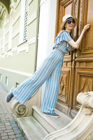Teenaged girl in jumpsuit dress is knocking on vintage wooden door of old building