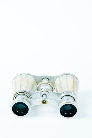Used binoculars with perl grips on white background, elegance tool for to watch entertainment closely