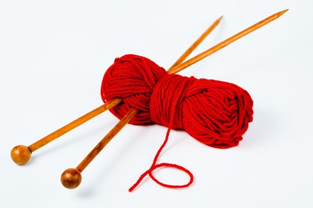 Pair of wooden knitting needles and red wool on white background Banco de Imagens