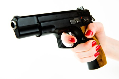 Big black semi automatic pistol with wooden grip in small woman's hand with manicure