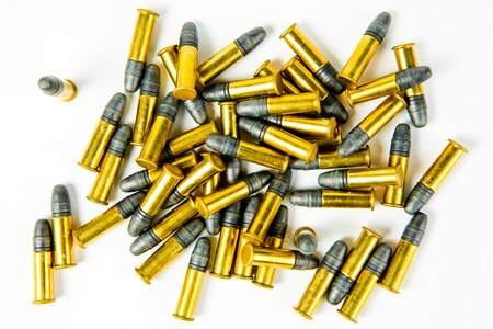 Bunch of small rim fire ammunition, yellow brass and gray lead on white background