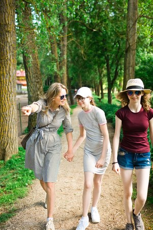 Mother is showing to daughters interesting thing during trip in nature Imagens