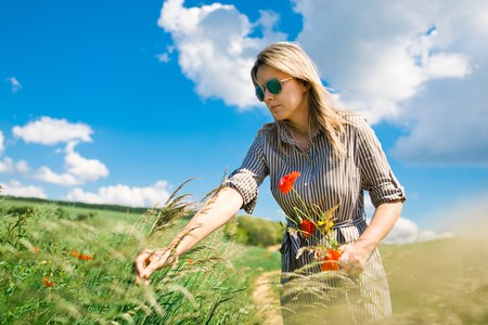 A woman in sun glasses is plucking a poppy picking a bouquet of wildflowers in a meadow Stock Photo