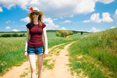 Young girl in short jeans and poppy flower in hat is walking on cart road within colorful nature during spring