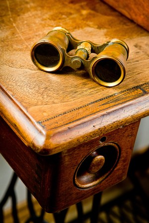 Vintage brass binoculars on old wooden table, scratches on surface