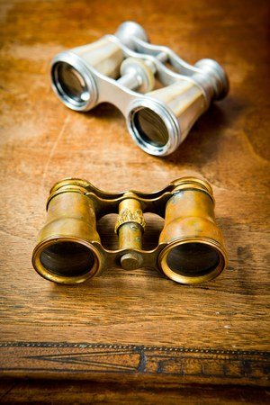 Vintage brass and silver binoculars on old wooden table, scratches on surface