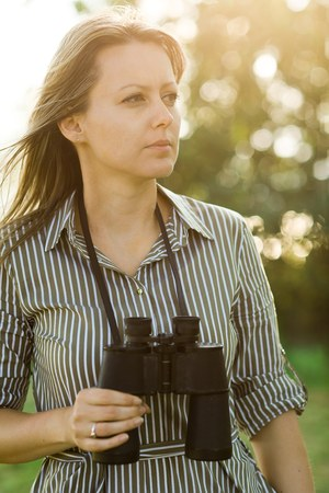 Attractive young tourist with binoculars outdoor in forest during sunset Stock Photo