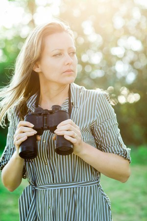 Attractive woman having binoculars outdoor in nature during sunset Stock Photo