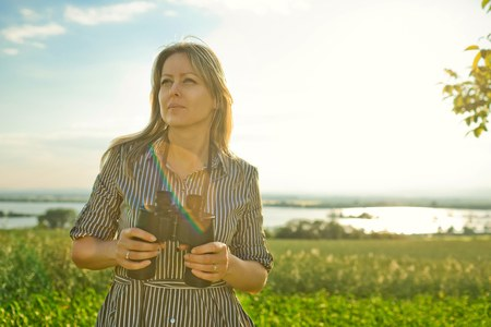 A woman explorer holds black binoculars outdoor in nature during sunset Stock Photo