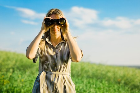A woman is using black binoculars outdoor in nature during sunset Stock Photo