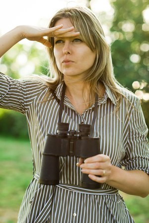A woman look into distance covering eyes, holding binoculars in the hand