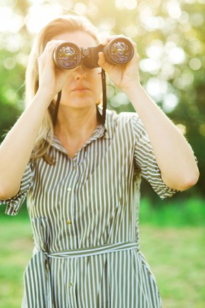 A female observer is using black binoculars outdoor in park before sunset
