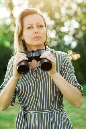 A woman explorer is going to use black binoculars outdoor in nature during sunset