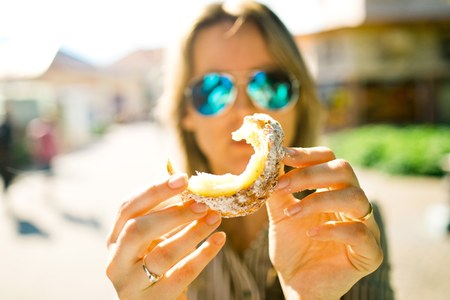 Sweet temptation, woman is going to eat piece of Trdelnik, traditional cake sprinkled with sugar