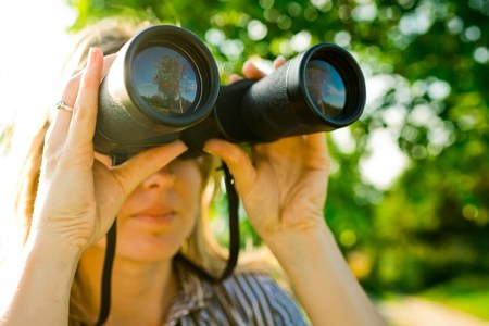 A woman explorer is using black binoculars outdoor in nature during sunset