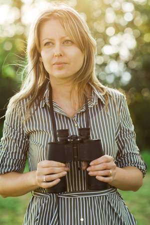 A female tourist explorer with binoculars stays outdoor in nature during sunset